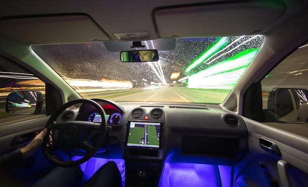 Мужчина водит машину по городскому шоссе. вечер в ночное время