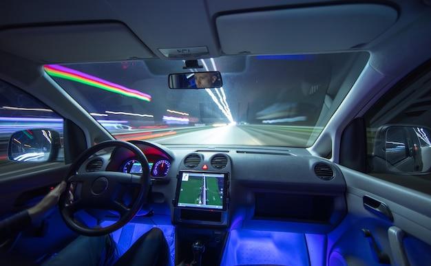 Мужчина водит машину по городской дороге. вечер в ночное время