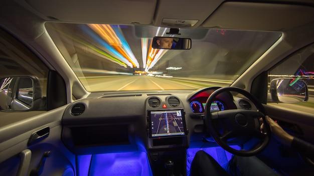 Мужчина водит машину по городской дороге. левостороннее движение. вечер в ночное время