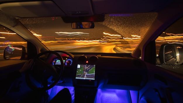 Мужчина едет с gps по ночной дороге. вид изнутри. широкий угол