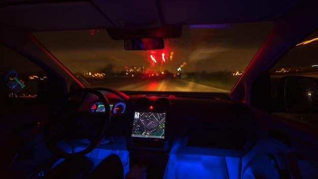 Мужчина едет с картой по дождливому шоссе. вечер в ночное время. вид изнутри