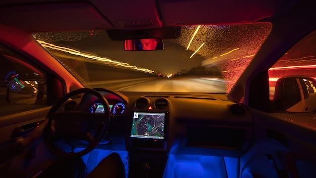 남자는 비오는 길에 지도를 들고 운전합니다. 저녁 밤 시간입니다. 내부 모습