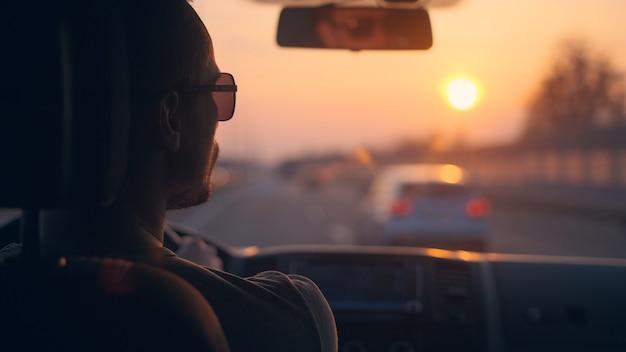 夕日の背景に都市高速道路に沿って自動車を運転する男