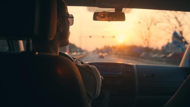 都市高速道路で自動車を運転している男