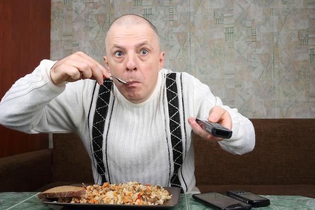 男はピラフを食べてテレビ番組を見つめる