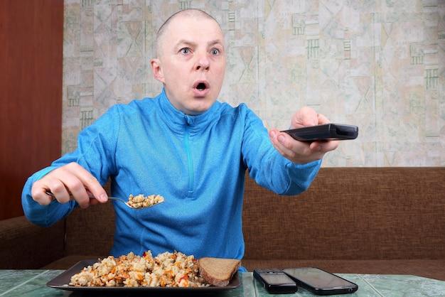 Мужчина ест плов из риса и смотрит телепрограмму