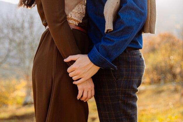 Мужчина нежно держит женщину за руку