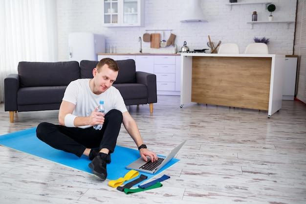 남자는 집에서 스포츠를 하러 간다. 운동선수는 집에서 바닥에 앉아 물을 마신다, 건강한 생활 방식