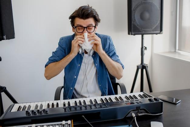 その男は病気になった。彼は鼻をかむ。レコーディングスタジオの作曲家。音楽制作技術、。男はレコーディングスタジオでサウンドミキサーや放送スタジオでdjに取り組んでいます。