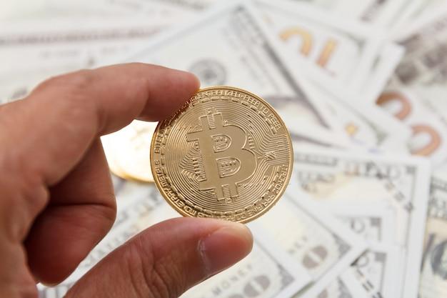 モックアップ現金の上にビットコインを持ち上げる男の手。暗号通貨デジタルマネーの概念