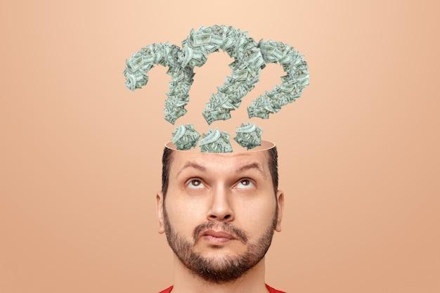 그 남자는 지폐, 미국 달러로 만든 그의 머리에 물음표가 있습니다. 금융 위기, 파산, 저축, 공포, 신용, 부채, 수입 검색의 개념.