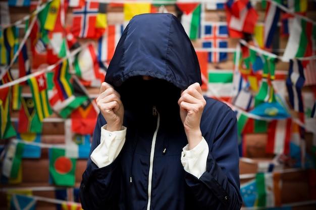 남자는 재킷 후드로 얼굴을 숨깁니다. 그림자 경제 개념입니다.