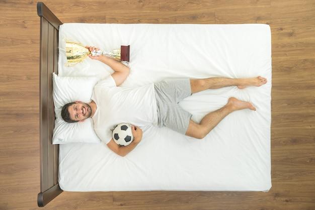 Мужчина держит на кровати металлическую чашку. вид сверху