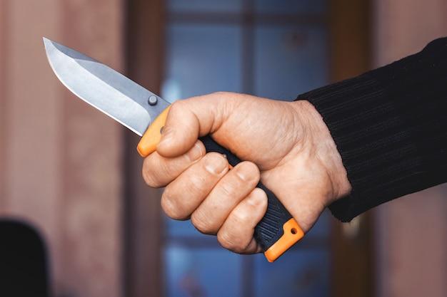 남자는 방에서 손에 칼을 들고