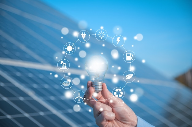 Мужчина держит лампочку, светодиодную лампочку на фоне солнечных батарей с иконками источников энергии для возобновляемых источников, устойчивого развития
