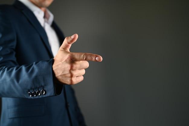 남자는 그의 앞에 검지 손가락을 쥐고있다. 양복 입은 남자가 검은 공간에 손가락을 앞으로 가리 킵니다. 개념 : 버튼을 클릭하여 지정하십시오. 고품질 사진