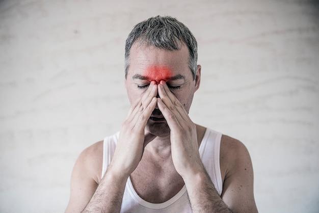 男性は、前額領域の頭の痛みから明らかな痛みを伴って指で鼻および鼻洞領域を保持する。副鼻腔の痛み