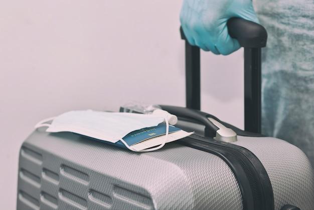 Мужчина держит в руке паспорт с билетом на поезд и медицинскую маску в латексных перчатках, что является незаменимой вещью во время путешествия после коронавируса-19.
