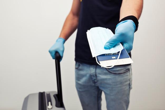 Мужчина держит паспорт с билетом на поезд и медицинскую маску