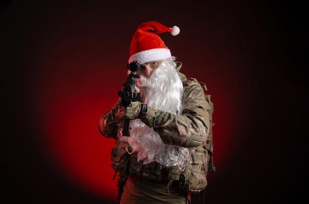 銃とサンタクロースの帽子をかぶった軍服を着た男 Premium写真