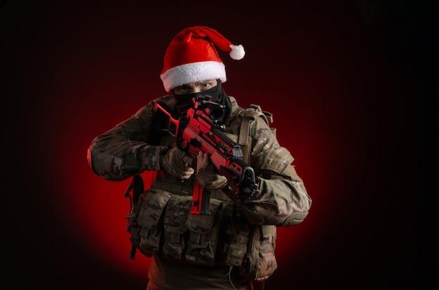 銃とサンタクロースの帽子をかぶった軍服を着た男