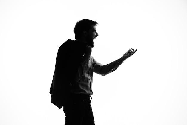 感情のシルエットの明るい背景の手にスーツ銃の男。高品質の写真