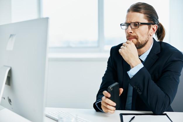彼の手のコンピューターでジェスチャーのオフィスでスーツを着た男