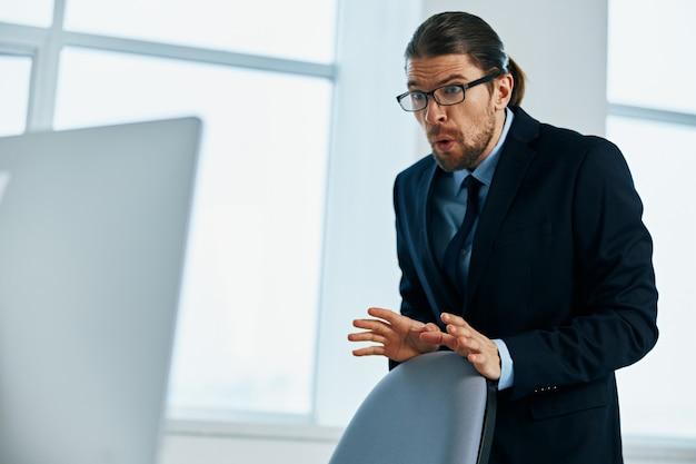 彼の手の幹部とジェスチャーでオフィスでスーツを着た男