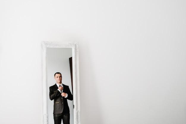 Мужчина в костюме смотрит на свое отражение в зеркале и дома поправляет галстук на рубашке. концепция одежды. готовимся к деловой встрече.