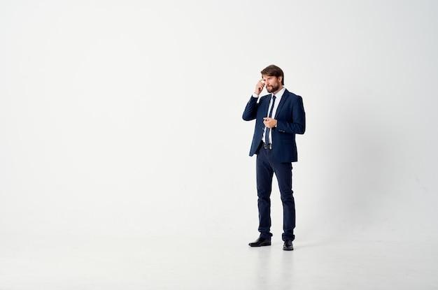 スーツの動きの男は明るい背景をジャンプします