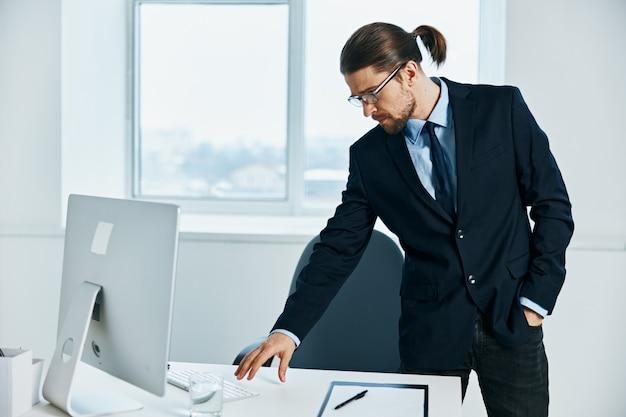 デスクトップワークプロセスコンピュータの近くでスーツを着た男