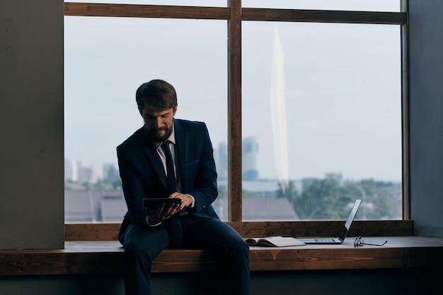 ノートパソコンのオフィスと窓の近くのスーツを着た男