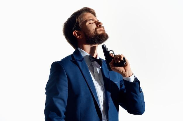 Человек в костюме с пистолетом в руке криминальный детектив убийца светлом фоне