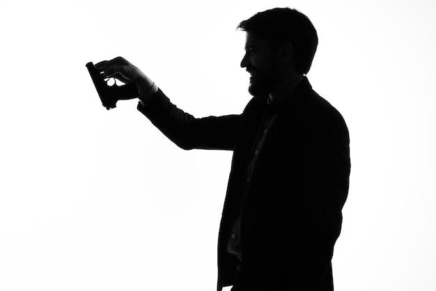 손에 권총을 든 정장을 입은 남자 범죄 손 제스처 밝은 배경