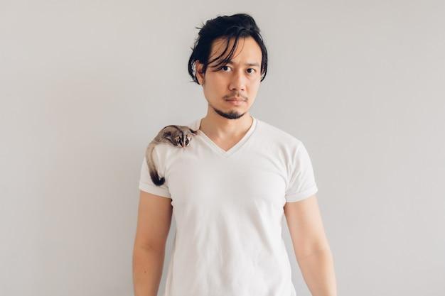 白いtシャツを着た男性は、ペットをホルダーに乗せて立っています。