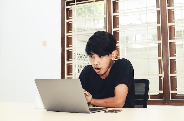 Мужчина в черной азиатской футболке с шокированным выражением лица сидел перед ноутбуком.