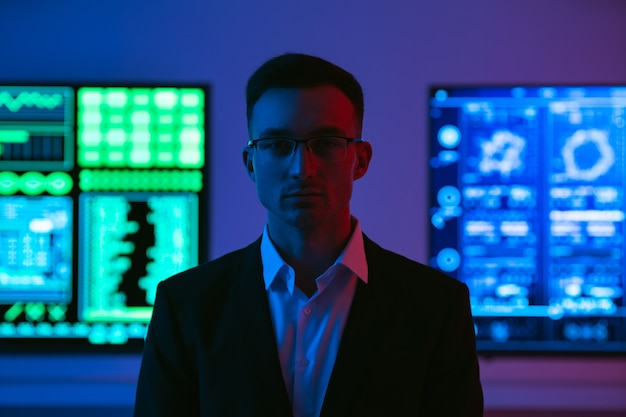 Человек в очках, стоящий на фоне экранов
