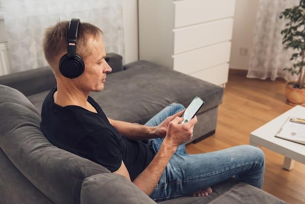 Мужчина в наушниках и со смартфоном сидит на диване. вид сзади.