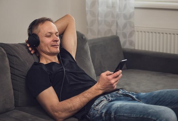 Мужчина в наушниках и со смартфоном сидит на диване.