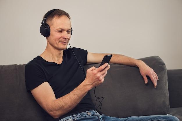 헤드폰을 쓰고 스마트 폰을 든 남자가 소파에 앉아있다.