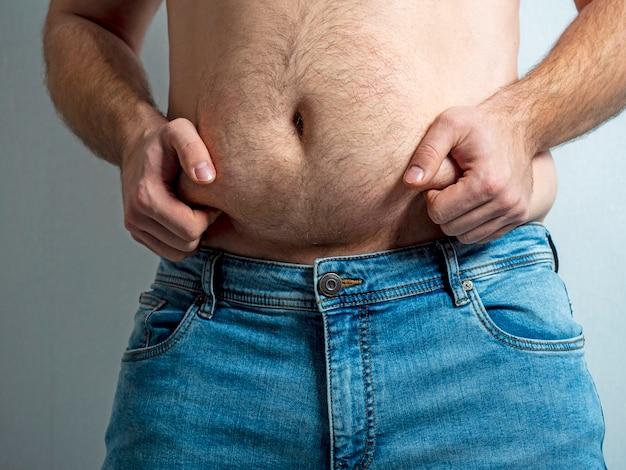ジーンズをはいた男は、毛むくじゃらでたるんだ太ったお腹を圧迫します。栄養不良の概念。ボディポジティブ。自己の受け入れ