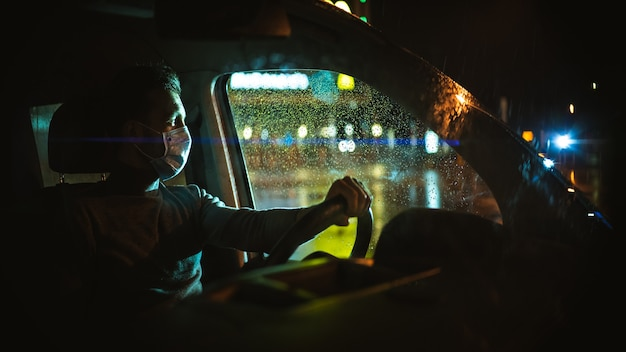 의료용 마스크를 쓴 남자는 밤 도시 도로에서 차를 운전합니다.