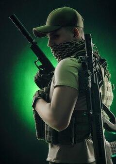 Мужчина в военной спецодежде позирует с пистолетом в руках на темном фоне в дымке