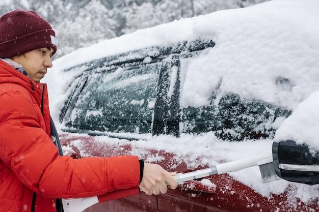 Мужчина в красном пальто чистит машину щеткой во время снегопада