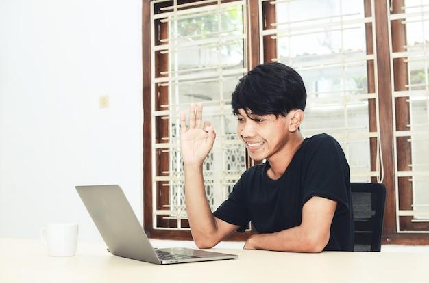 黒のアジアンシャツを着た男性がビデオ通話でノートパソコンの前に座っていた