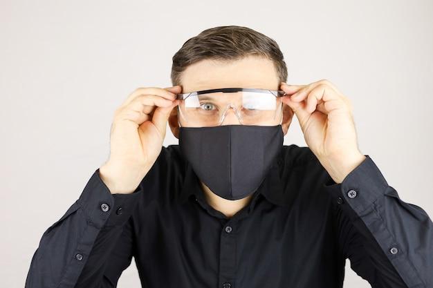 黒いシャツを着た男は白い背景に医療眼鏡をかけていました