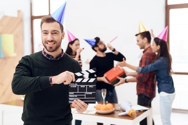 Человек в кепке держит фильм с 'хлопушкой'.