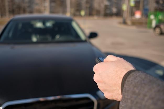 코트를 입은 남자가 키 체인을 차에 보내 알람을 켰습니다.
