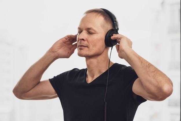 Мужчина в наушниках любит слушать музыку.