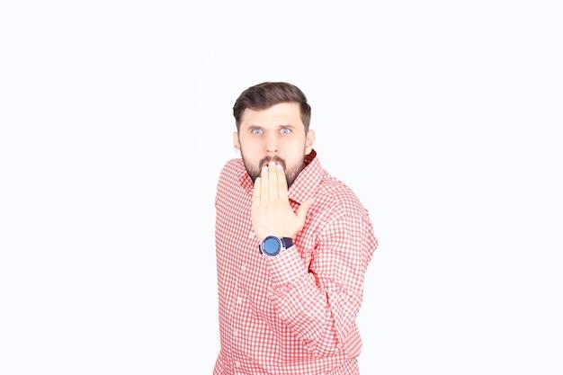 분홍색 체크 무늬 셔츠를 입은 남자가 입술에 손을 올렸다. 남자가 입에 손을 대고